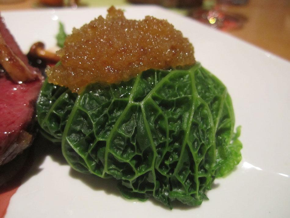 Rosa gebratener Hirschkalbsrücken und zartes Ragout aus der Keule mit gefülltem Wirsingkohlköpfchen, frischen Preiselbeeren und Kartoffelsoufflé