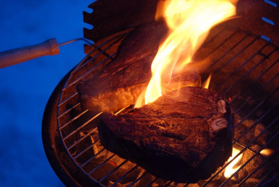 Dry aged Porterhouse T-Bone Steak auf dem heißen Holzkohle-Grill