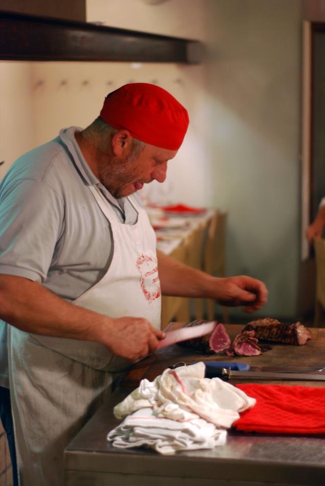 Der Koch beim Steak schneiden