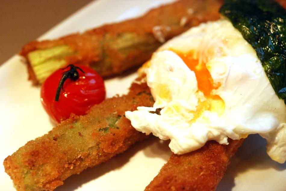 Panierter grüner Spargel mit pochiertem Ei und Pinienkernen